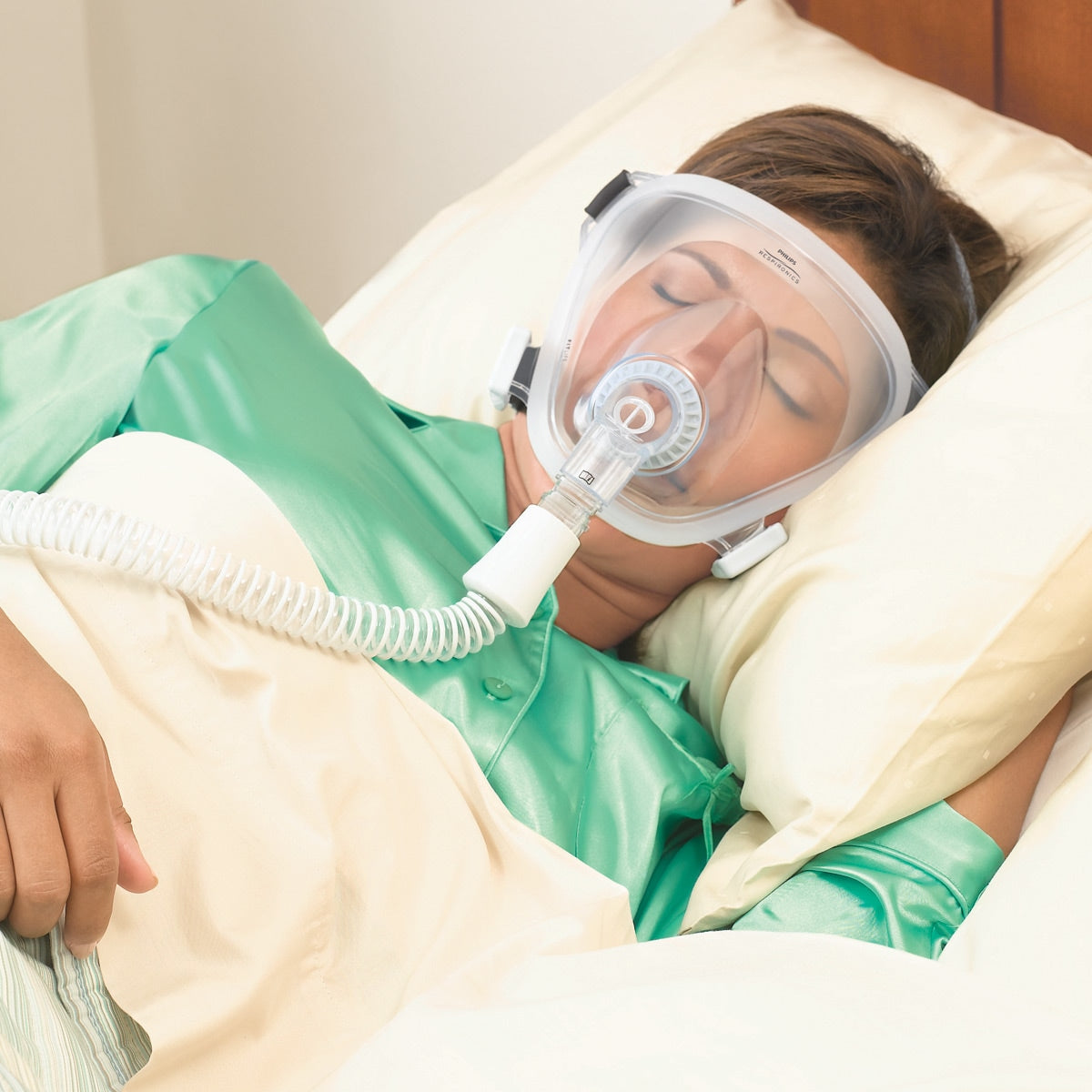Woman sleeping in green pajamas using the FitLife Total Face CPAP Mask With Black Headgear by Phillips Respironics.
