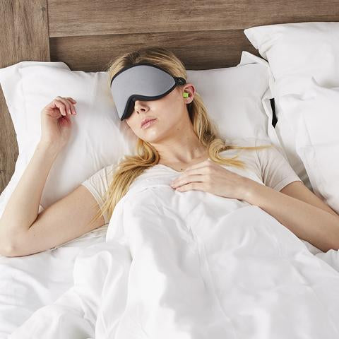 Woman sleeping with green earplugs and the Blockout Shade Mask in grey color.