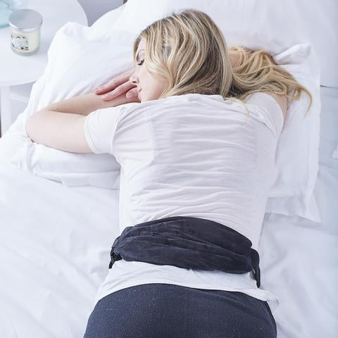 Woman sleeping with Ebony Aromatherapy Multi-Purpose Wrap in black with straps place in her low back.