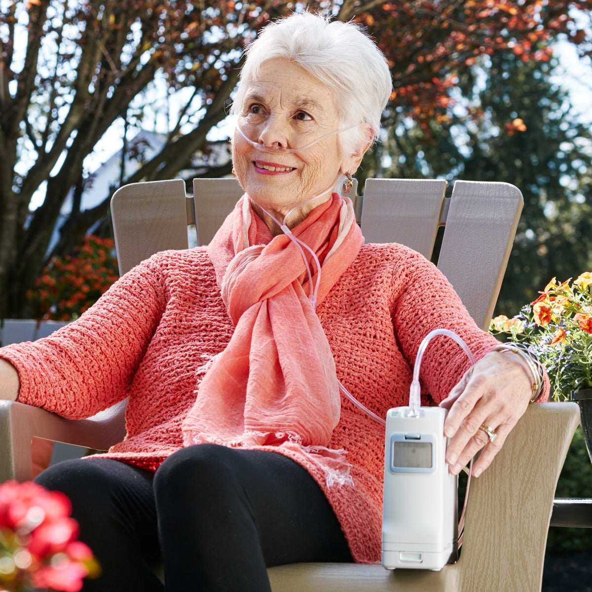 Woman Sitting With The Inogen One G4 Portable Oxygen Concentrator.