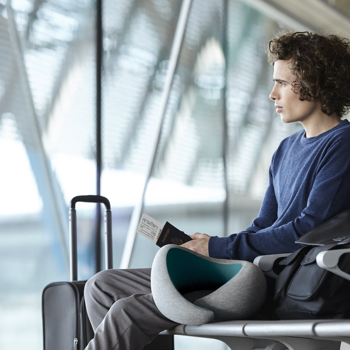 Man Waiting For Flight With Neck Pillow.