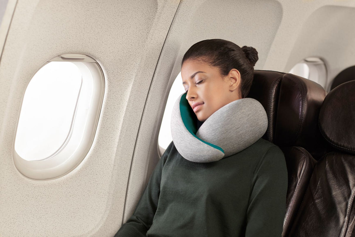 Woman Sleeping On Plane With Neck Pillow.