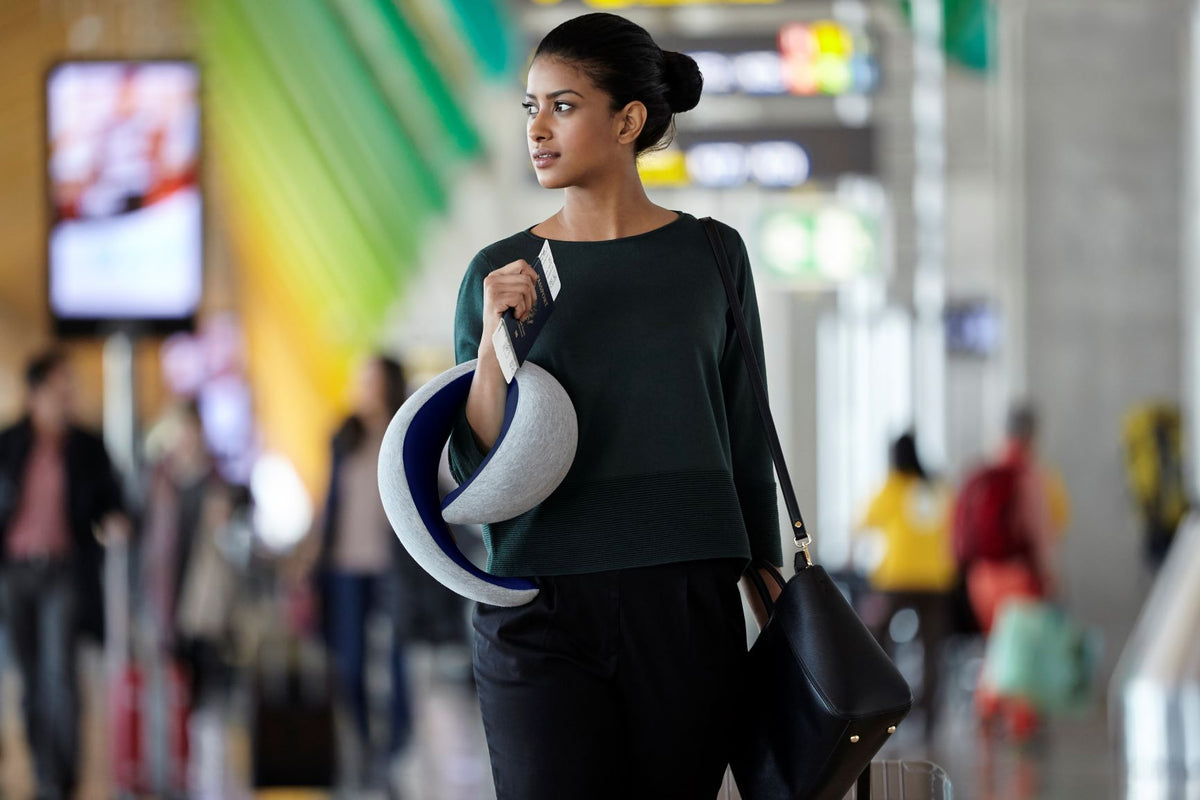 Woman Traveling With Deep Blue Neck Pillow Go.
