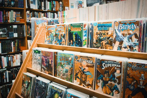 comic book stand with Batman, Superman, Aquaman and other titles