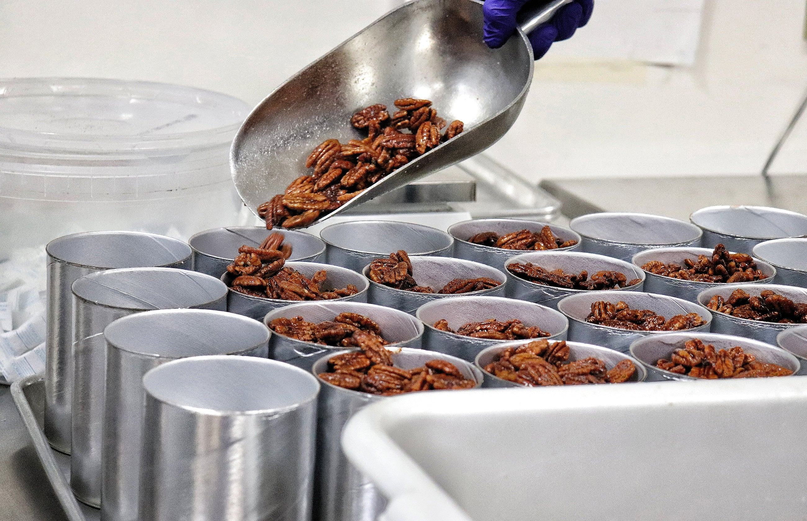 Nutkrack pecans being scooped into cans