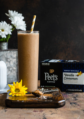 A portrait of a Vanilla Cinnamon Coffee Smoothie in a tall glass with a straw, and a box of Peet's Flavored K-Cups Vanilla Cinnamon flavor in the background.