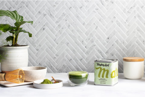 A countertop with a tin of Mighty Leaf Organic Mint Matcha, as well as a cup of Organic MInt Matcha and a matcha whisk.