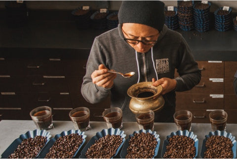 A photograph of a roaster at the Peet's Roastery cupping freshly roasted coffee