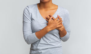 a woman putting her hands over her heartburn