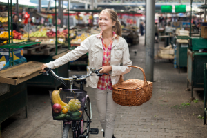 woman on her bicycle shopping at a farmers market, for a greener lifestyle