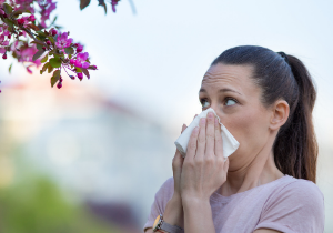 woman with common spring allergies blows her nose outdoors