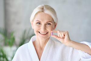 Woman taking vitamins for women over 50