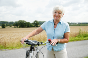 woman bicycling - stay active to feel younger