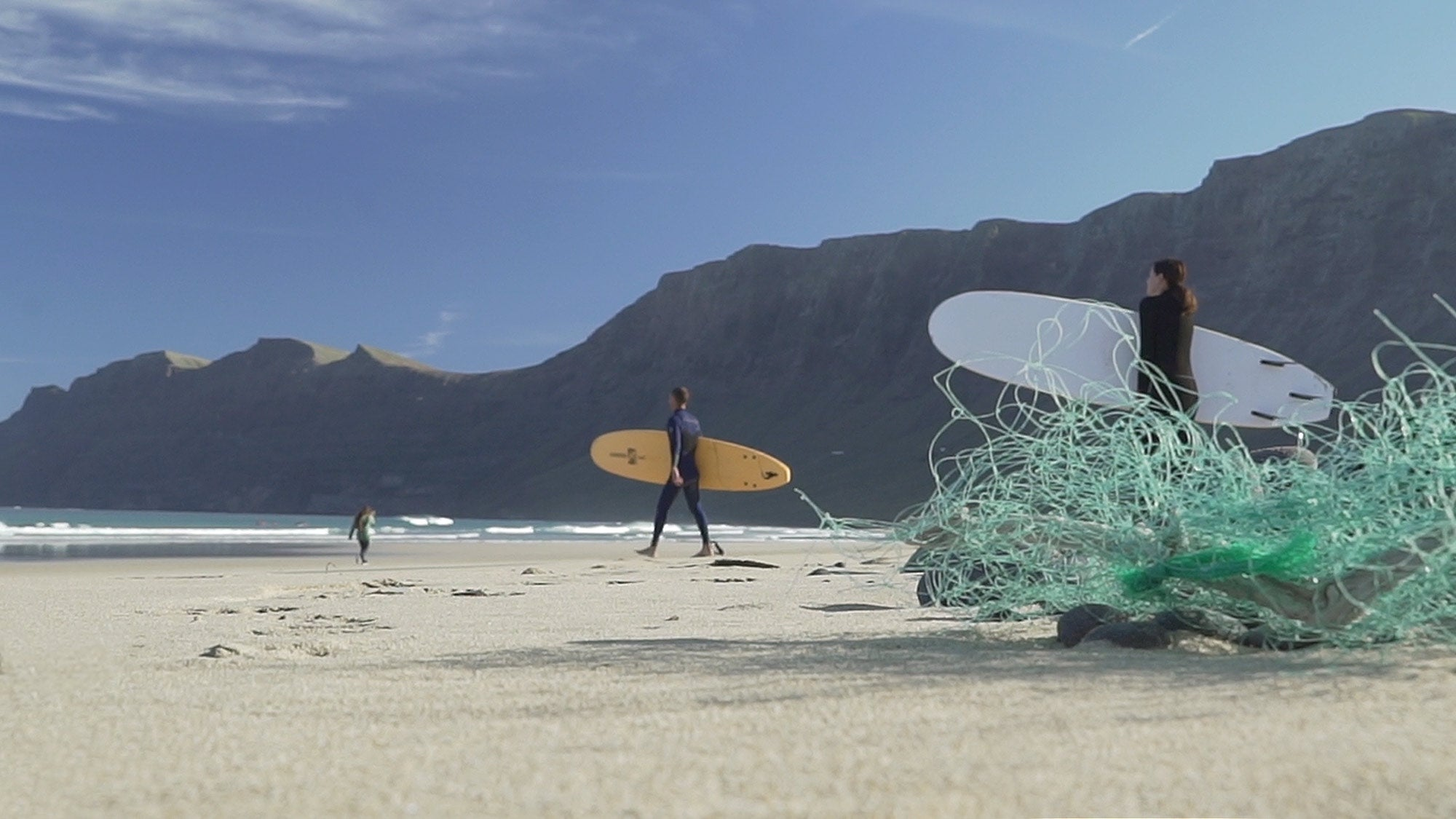 Surfers walking towards the waves, fishing nets in foreground