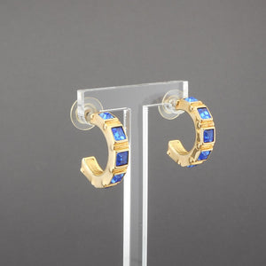 "This is a circa 1990 pair of half hoop earrings by Swarovski. Gold tone, square faux sapphire stones. The swan mark is impressed on the inside surface of the hoop.  Each approximately 1/4"" x 1"" h  Excellent vintage pre-owned condition - barely, if ever, used FREE US Shipping via USPS standard shipping"