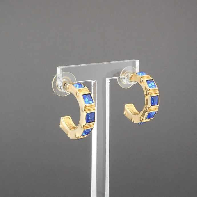 This is a circa 1990 pair of half hoop earrings by Swarovski. Gold tone, square faux sapphire stones. The swan mark is impressed on the inside surface of the hoop.  Each approximately 1/4