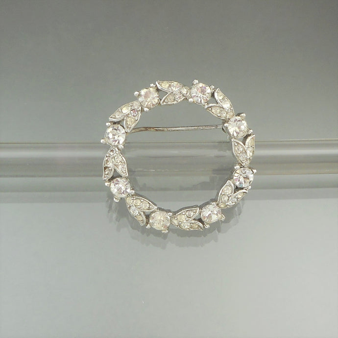 This is a circa 1940 brooch by Crown Trifari. Clear rhinestones in a floral wreath design in a silver tone setting.
