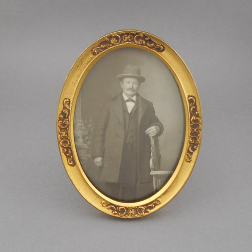 Antique Edwardian Gold Picture Frame, gilded steel in an oval shape with an impressed design. Glass in place, it holds a studio portrait photograph of a man wearing a coat and hat. Patent date 1908. Antique condition, with expected minor scratches on the frame and finish loss on the reverse.  FREE US Shipping