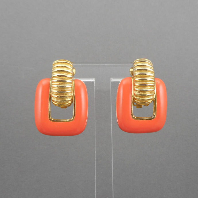 This is a circa 1960 pair of clip earrings by Gay Boyer. Door knocker design in gold tone with coral enamel. Each approximately 7/8