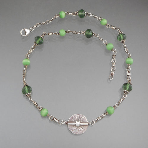 Vintage Handcrafted Collar Necklace. A sterling silver flower design charm on a chain with green beads. Faceted crystal style and cats eye beads. Artist unknown.   Approximately 5/8