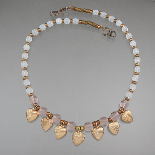 Vintage Handcrafted Collar Necklace. Gold tone heart shaped charms with opalescent and pale pink glass beads. Artist unknown. Approximately 3/4