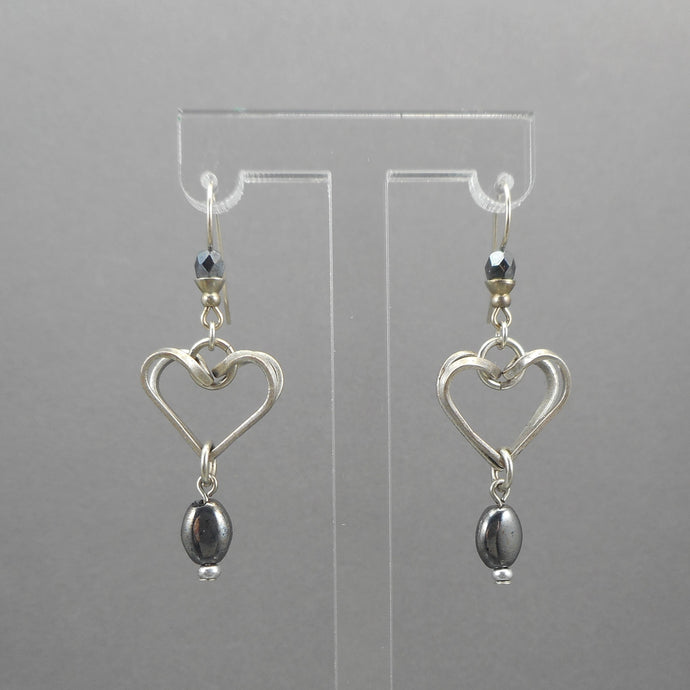 A circa 1990 pair of heart design dangle earrings with hematite beads. Pewter tone finish with wires for pierced ears.  Each approximately 5/8