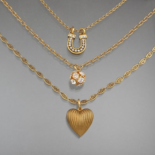 This is a charm necklace by John Wind / Maximal Art. Three chains, each with a different charm. Luck and Love themed with a horseshoe and a heart. Signed on the reverse of the horseshoe. Gold tone finish with rhinestones.  Approximately 5/8