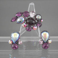 Load image into Gallery viewer, This is a circa 1950 jewelry set by Regency, New York, NY.  Brooch and clip-on earrings with purple rhinestones and glass cabochons, clear and aurora borealis, in pewter tone settings.