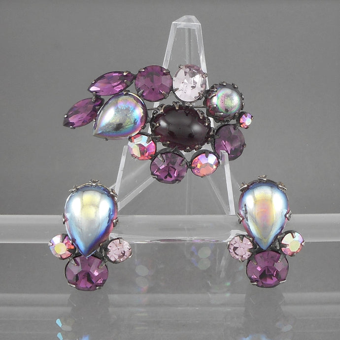 This is a circa 1950 jewelry set by Regency, New York, NY.  Brooch and clip-on earrings with purple rhinestones and glass cabochons, clear and aurora borealis, in pewter tone settings.