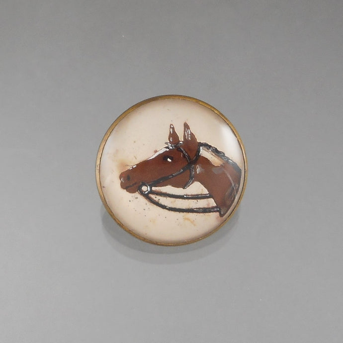 An antique Victorian Bridle Rosette. Intaglio Essex Crystal, reverse painted with an image of a horse head. Domed glass top on brass.  Approximately 1 1/4