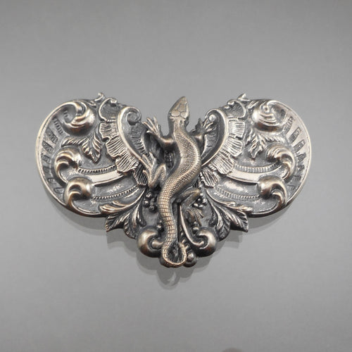 This is a Silverplate Victorian Era Belt or Cape Buckle. Circa 1890. A lizard sits atop elaborate Rococo style embossing. The stampings are brass with silver plating and can be attached to a sash, belt, cloak or cape. Antique pre-owned condition with tarnish and plate loss, particularly on the reverse. FREE US Shipping