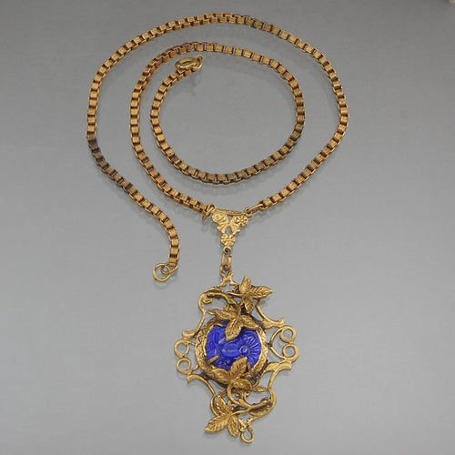 This is a Victorian Era lavalier necklace. Circa 1890. Rolled gold, flower and leaf design with cobalt blue Czech glass on a box chain.  Pendant approximately 1 1/4
