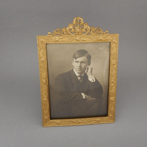 Antique Victorian or Edwardian Table Top Easel Picture Frame, floral pattern with an ornate cresting. * Possibly brass (it has a painted gold finish) with convex glass, it holds a photograph of a young man. Marked