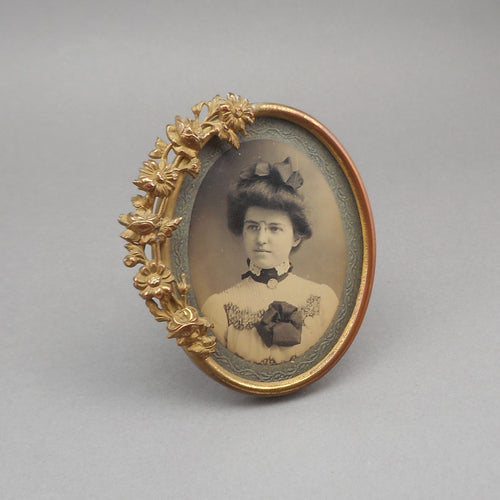 Antique Victorian Gilded Table Top Easel Picture Frame, oval shape with a garland of flowers and leaves. Glass in place, it holds a photograph of a girl wearing pince-nez eyeglasses.  Approximately 3 1/8