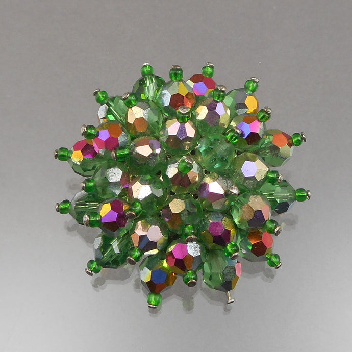 This circa 1950 flower design brooch is a cluster of green glass beads with an aurora borealis finish and small glass seed beads.  Approximately 2