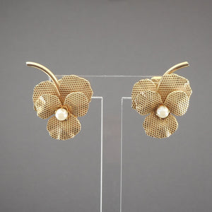This is a circa 1950 pair of clip on flower earrings . Violet or pansy design with faux pearl centers in textured gold tone petal settings.