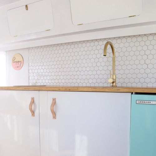 Caravan kitchen with hexagon peel and stick tiles and mint glossy vinyl wrapped fridge