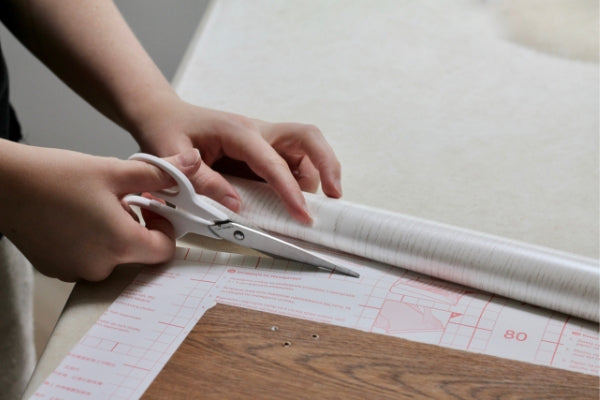 Hands holding white scissors cutting vinyl using backing paper grid as a guide