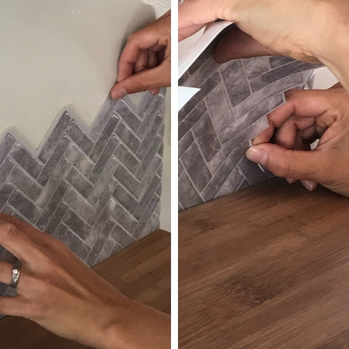 Grey herringbone peel and stick tiles being applied onto white wall above oak benchtop