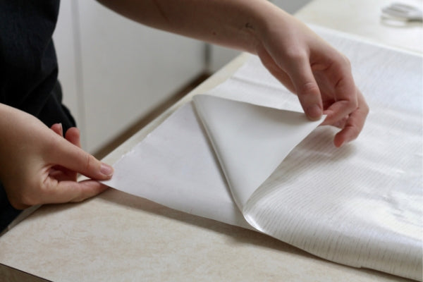 hands folding a corner of sticky back plastic away from backing paper