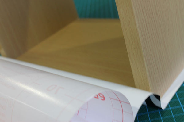 Blonde wood box shelf with vinyl being applied