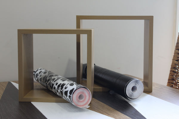 2 boxed shelves with black and white vinyl rolls peeking out