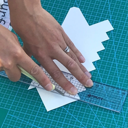 Hands cutting peel and stick tiles with craft knife along a metal edge ruler on a green craft mat