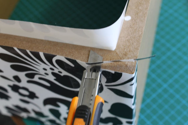 black and white flower vinyl being trimmed in corner with craft knife
