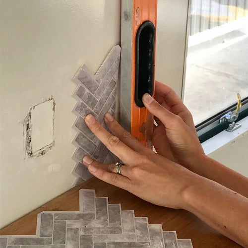 Hands checking angle of grey peel and stick chevron tiles with an orange level in caravan kitchen
