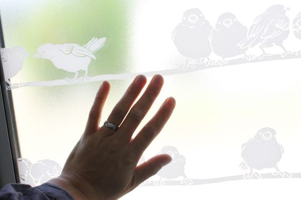 left woman hand on window film with white sparrow pattern