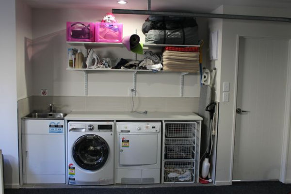 white laundry with storage shelves above