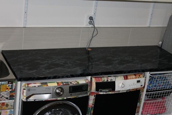 laundry covered with colourful vinyl and black marble bench top