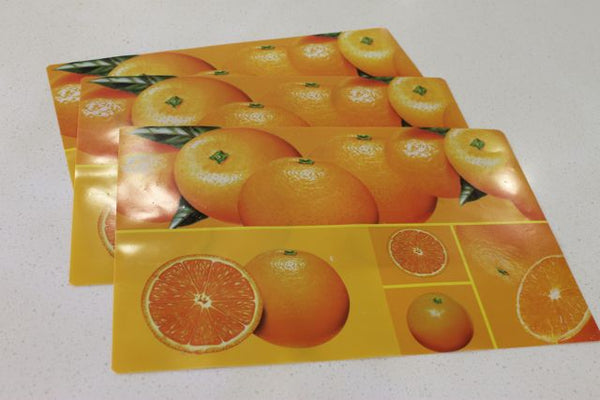 oranges patterned placemats laid flat on bench