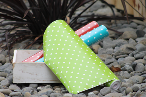 green, blue and red polkadots vinyl rolls in white rustic tray outside